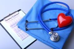 Le cardiogramme avec le stéthoscope médical et le coeur rouge avec le docteur enduisent sur la table photos libres de droits