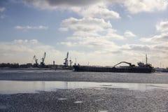 Le cargo de logistique et de transport avec des ports tendent le cou le pont venant dans le port photographie stock