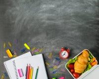 Le carnet éducatif d'approvisionnements de sandwich parque les agrafes colorées de crayons sur un panneau de craie Concept de nou image stock