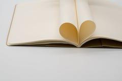 Le carnet avec des pages s'est plié dans un coeur d'isolement sur le backgr blanc Photographie stock libre de droits