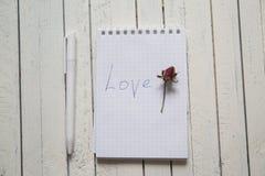 Le carnet avec l'inscription de marqueur je t'aime et s'est levé sur le blanc Photographie stock libre de droits