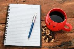 Le carnet avec les grains de café rouges de tasse de café et au coeur forment Photographie stock libre de droits