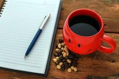 Le carnet avec les grains de café rouges de tasse de café et au coeur forment Photo libre de droits