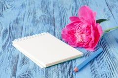 Le carnet avec un crayon et des pivoines fleurit sur le backgro en bois Photographie stock