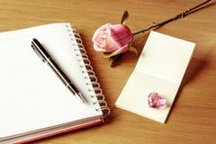 Le carnet blanc vide avec s'est levé Photographie stock libre de droits