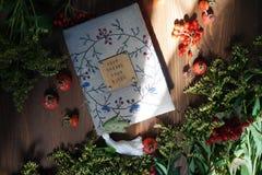 Le carnet brodé de travail manuel parmi des hanches, des plantes et des fleurs Images libres de droits