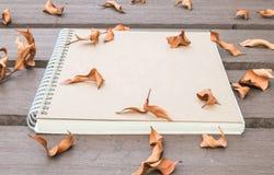 Le carnet brun de plan rapproché sur la table en bois dans le jardin avec les feuilles sèches a donné au fond une consistance rug Images libres de droits