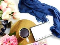 Le carnet de tasse de café de matin avec des fleurs et l'écharpe sur la copie espacent le fond blanc Photographie stock libre de droits