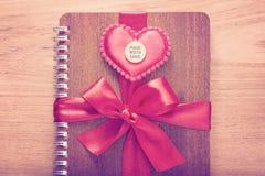 Le carnet enveloppé avec le ruban rouge, rouge a senti des coeurs avec fait avec Image libre de droits