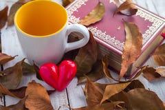 Le carnet et le brun part avec l'icône de coeur et la tasse de café Image libre de droits