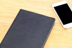 Le carnet et le mobile vides noirs étroits sur la table en bois, raillent pour ajouter votre contenu Photos stock