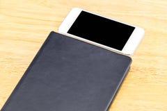 Le carnet et le mobile vides noirs étroits sur la table en bois, raillent vers le haut des FO Photographie stock libre de droits
