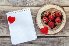 Le carnet et les fraises vides à un coeur ont découpé dans le bois Images libres de droits
