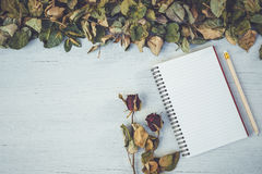 Le carnet et sèchent la fleur rose sur la plate-forme en bois blanche avec la station thermale vide Photographie stock libre de droits