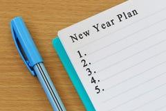 Le carnet et le stylo placés le bureau en bois et la nouvelle année prévoient le texte images stock