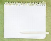 Le carnet a orné avec de petites fleurs blanches et stylo se trouvant sur le t Photo stock