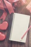 Le carnet ouvert de blanc avec le boîte-cadeau et le coeur rouge forment Photo stock