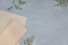 Le carnet, le papier et les fleurs roses sur le fond bleu photo stock