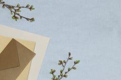 Le carnet rose, le crayon en bois et l'affûteuse, panier avec des fleurs sur le bureau bleu image stock
