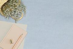 Le carnet rose, le crayon en bois et l'aff?teuse, panier avec des fleurs sur le bureau bleu photo stock