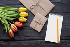 Le carnet vide, le crayon et les tulipes jaunes et rouges fleurit sur le fond en bois de vintage Foyer sélectif Place pour le tex Images stock