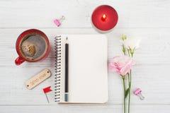 Le carnet vide, tasse de café, a allumé la bougie, fleurs Photographie stock libre de droits