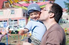 Le carrousel d'amusement de père et de fils joyeux vont rond Image stock