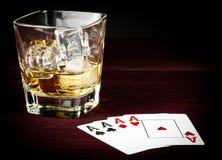 Le carte da gioco del poker si avvicinano al vetro di wiskey Immagine Stock