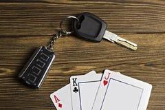 Le carte da gioco e le chiavi dell'automobile su un fondo di legno giocano immagine stock