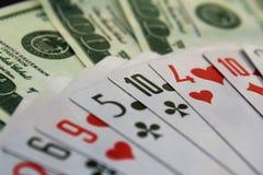 Le carte da gioco ed i dollari dei soldi sono sparsi fuori sulla tavola immagine stock libera da diritti