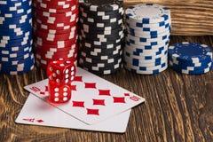 Le carte della mazza con i cubi meravigliosamente sono disposte sulla tavola, contro lo sfondo dei chip di mazza Immagine Stock
