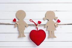 Le carton silhouette la fille et le garçon avec le coeur sur le Ba en bois blanc Images libres de droits