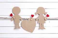 Le carton silhouette la fille et le garçon avec le coeur sur le Ba en bois blanc Photographie stock libre de droits