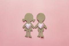 Le carton silhouette la fille et le garçon avec des coeurs sur le backgroun rose Photos stock