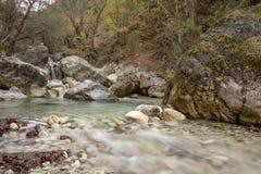 Le cascate e un fiume fra i massi di pietra sono coperti di muschio in una foresta di autunno della montagna immagine stock libera da diritti