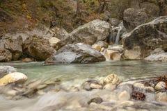 Le cascate e un fiume fra i massi di pietra sono coperti di muschio in una foresta di autunno della montagna fotografie stock