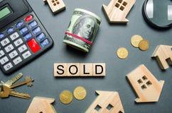 Le case di legno, un calcolatore, le chiavi, le monete ed i blocchi con la parola hanno venduto Concetto di vendita della casa, a fotografie stock libere da diritti