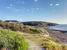 Le case di spiaggia su una scogliera alla baia di Hallett tirano Fotografie Stock Libere da Diritti