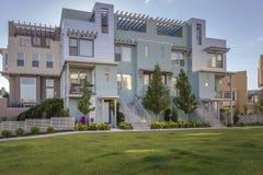 Le case moderne con erba fuori fronteggiano Immagine Stock