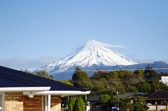 Le case suburbane sotto neve nevosa hanno ricoperto il supporto Egmont, Taranaki Nuova Zelanda immagine stock libera da diritti