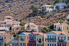 Le case variopinte tradizionali sulle rocce nell'isola Dodecane di Symi Immagine Stock