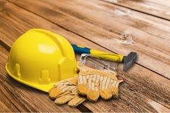 Le casque antichoc et le cuir jaunes fonctionnent des gants, marteau Image libre de droits