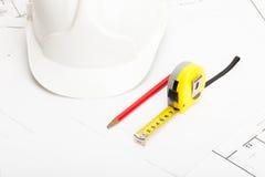 Le casque blanc de construction avec le crayon et la bande de mesure - fermez-vous vers le haut du tir de studio photographie stock libre de droits