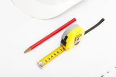 Le casque blanc de construction avec le crayon et la mesure attachent du ruban adhésif près de lui images stock