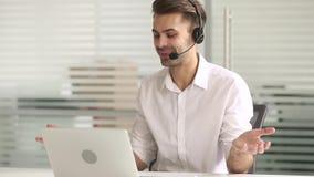 Le casque de port de téléprospecteur regardant l'ordinateur portable font à des affaires l'appel visuel banque de vidéos