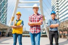 Le casque de sécurité d'usage de l'ingénieur industriel trois machinant la position avec des bras a croisé photo libre de droits