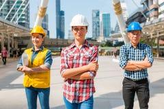 Le casque de sécurité d'usage de l'ingénieur industriel trois machinant la position avec des bras a croisé sur le bâtiment dehors images libres de droits