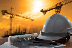 Le casque de sécurité et le pland d'architecte sur la table en bois avec le coucher du soleil scen image stock