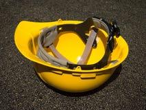 Le casque jaune pour la sécurité au chantier de construction Photographie stock libre de droits