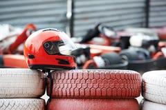 Le casque rouge avec le pare-soleil est sur des pneus image libre de droits